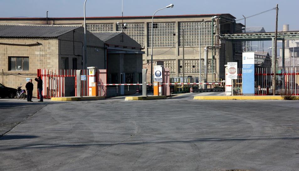 Dos homes esperen a l'entrada de la fàbrica d'Ercros a Flix. Gener de 2016