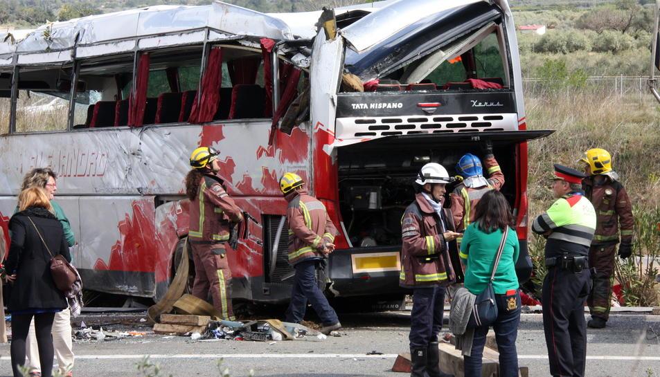 Els efectius d'emergències revisen l'autocar accidentat a l'AP-7 després de la seva reincorporació. Imatge del 20 de març de 2016
