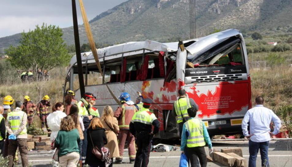 Efectius dels Bombers i Mossos observant l'autobús accidentat un cop la grua l'ha aixecat