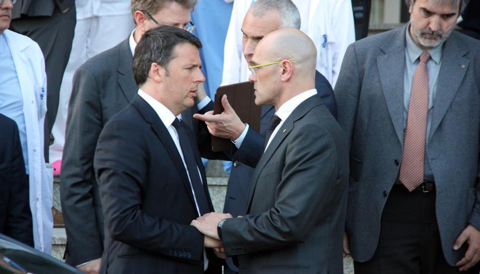 Pla mig del primer ministre italià, Matteo Renzi, agafant-se les mans amb el conseller Raül Romeva a les portes de l'Hospital Verge de la Cinta de Tortosa. Imatge del 21 de març de 2016