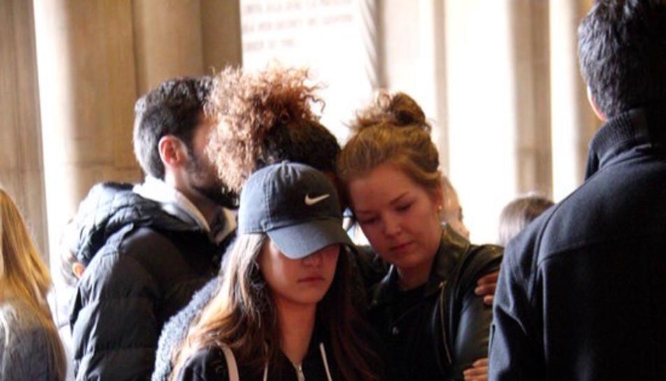 Tres estudiants de la UB s'abracen davant les flors en record de les víctimes de l'accident d'autobús de Freginals.