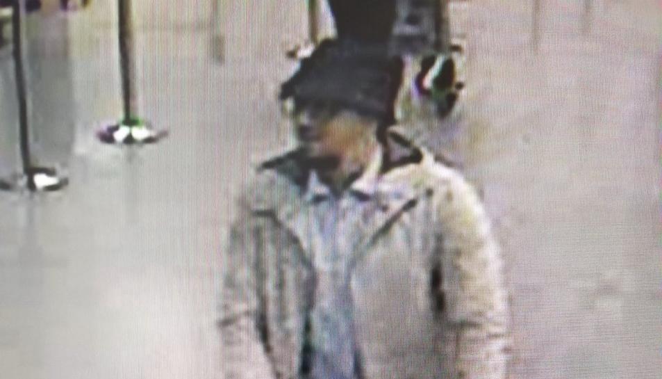 Imatge difosa per la policia belga del sospitós dels atemptats a l'aeroport de Brussel·les, on es veu un home amb jaqueta blanca i barret empenyent un portaequipatges.