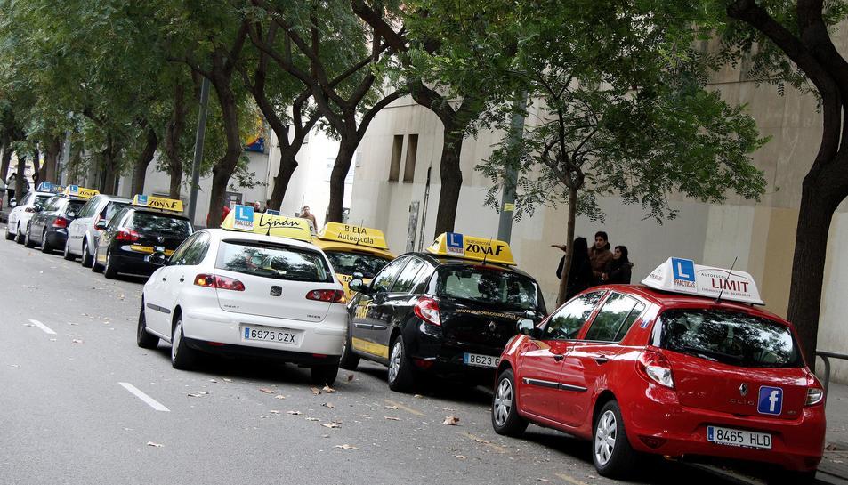 Un cotxe d'autoescola realitzant l'examen pràctic, mentre uns altres esperen el seu torn.
