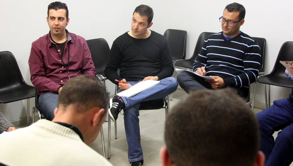 Imatge d'arxiu d'una teràpia de grup de Projecte Home a Tarragona, amb dos usuaris d'esquena i, al fons, el terapeuta del grup i dos usuaris més.