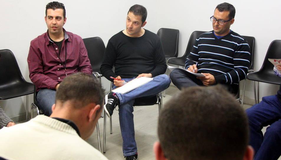Teràpia de grup de Projecte Home a Tarragona, amb dos usuaris d'esquena i, al fons, el terapeuta del grup i dos usuaris que hi participen, en Juan Manuel (centre) i en Miguel Ángel (dreta).