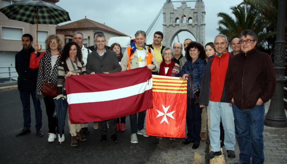 Foto de família del periodista letó Otto Ozols amb representant de l'ANC de les Terres de l'Ebre i de l'Ajuntament d'Amposta davant del Pont Penjant de la capital del Montsià. Imatge del 4 d'abril de 2016