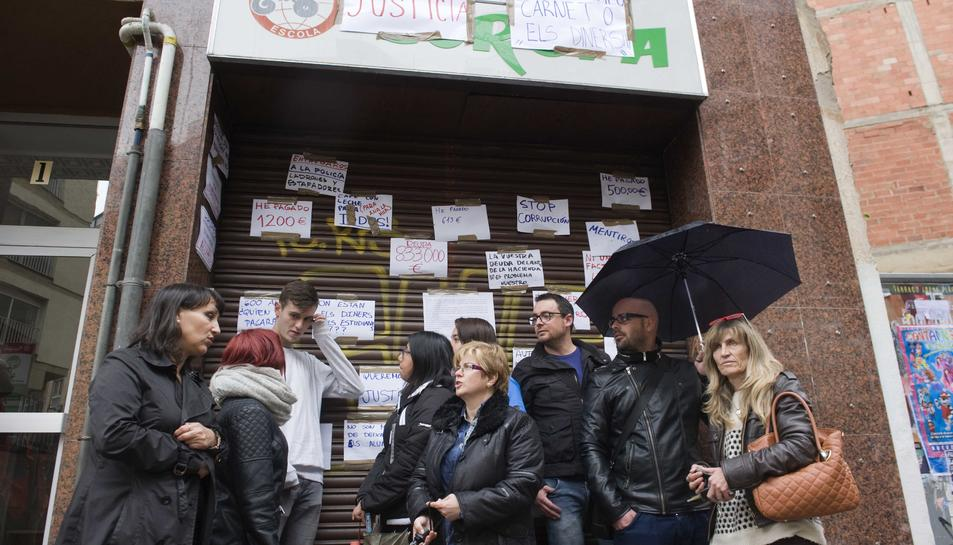 La pluja no va aturar la queixa d'alumnes i professors afectats, ahir al matí, davant del centre tancat.