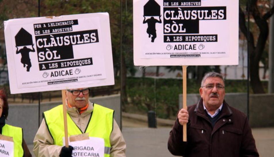 Dos membres d'Adicae amb pancartes aquest dimecres a la Ciutat de la Justícia de l'Hospitalet.