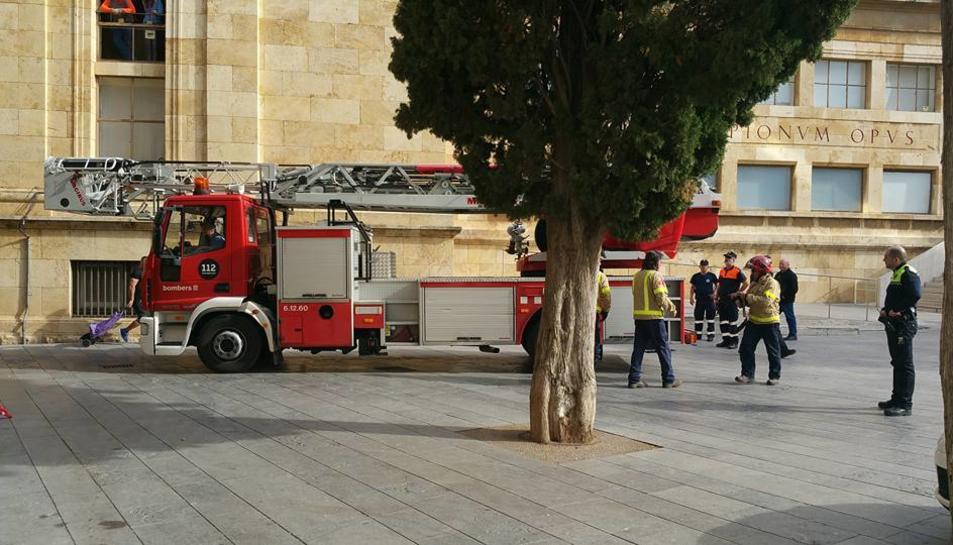 Moment en què una dotació dels Bombers sortia per la plaça del Rei, després de sanejar la façana.