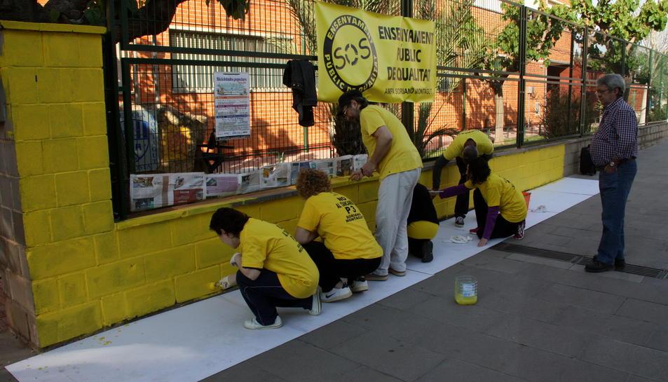 Un grup de mares i pares pintant el mur de l'escola Soriano Montagut d'Amposta. Imatge del 19 d'abril de 2016