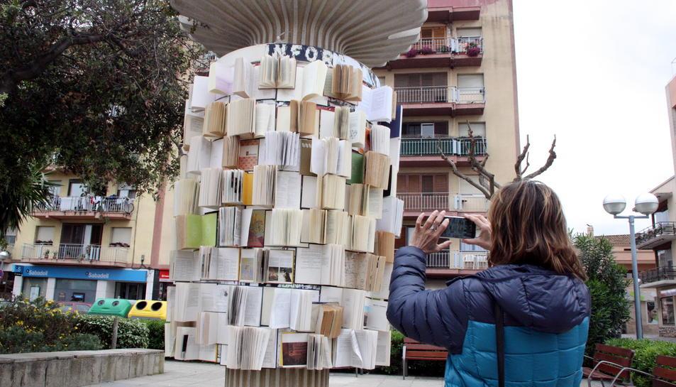 Una dona fotografiant un plafó publicitari folrat amb llibres a la Rambla Catalunya de Vila-seca, el 22 d'abril del 2016