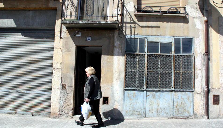 Pla obert del portal de l'immoble on s'ha produït l'homicidi, amb una dona caminant pel davant. Imatge del 24 d'abril del 2016
