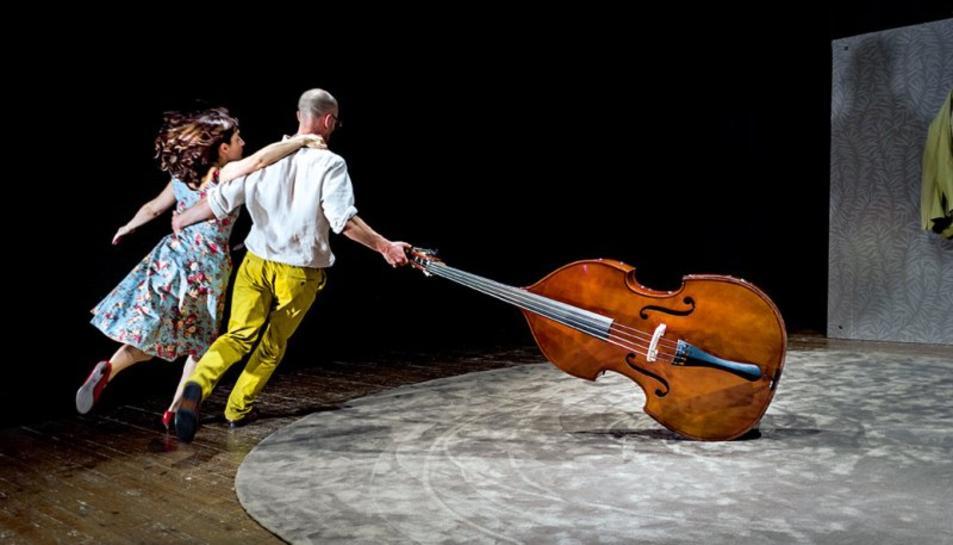 Imatge de l'espectacle 'Amigoo', de Mumusic Circus, en una escena divertida on un home i una dona dansen, agafats a un violoncel