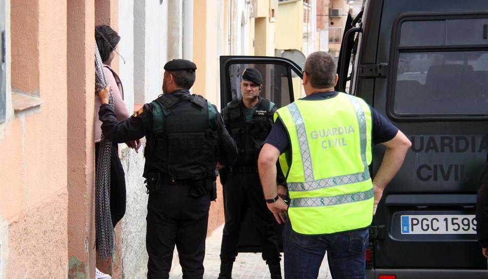 Una dona detinguda sortint d'un dels habitatges, al costat d'agents de la Guàrdia Civil, a Amposta, durant una operació contra el tràfic de drogues, aquest 12 de maig de 2016