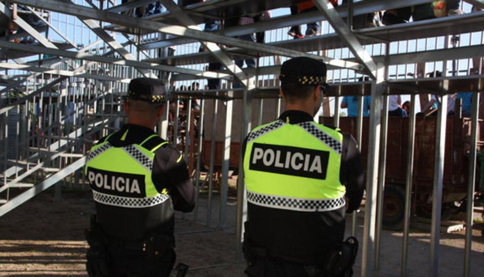 Dos agents de la policia local d'Alcanar, d'esquenes, a la plaça.