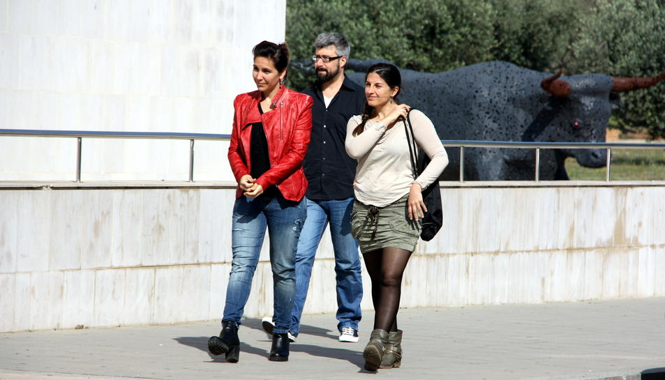 Les dues activistes d'AnimaNaturalis, Aïda Gascón i Yasmina Moreno, que van ser agredides al Mas de Barberans, arribant amb un company als jutjats d'Amposta, amb el gran bou que presideix una rotonda d'Amposta al darrera. Imatge 17 de maig de 2015. (Horit
