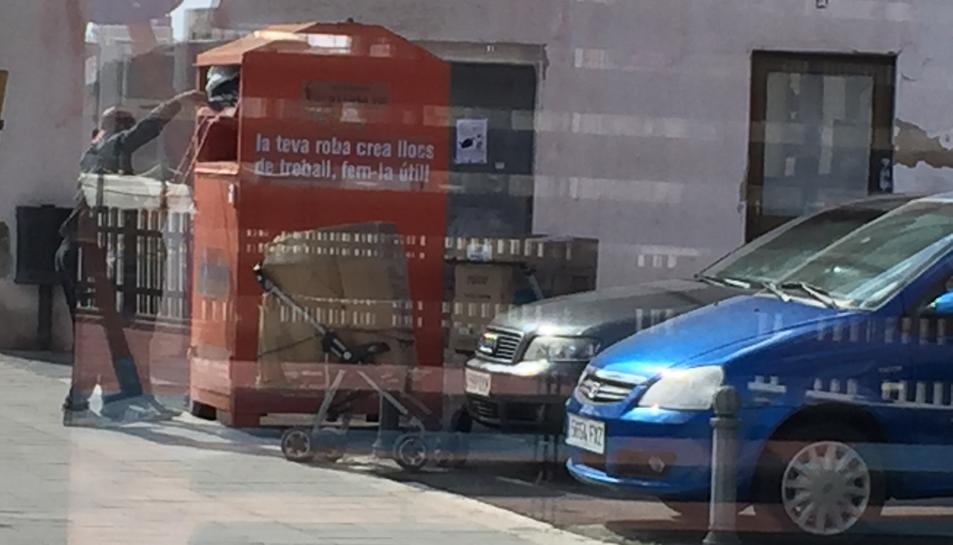 Imatge d'una persona agafant roba d'un contenidor.
