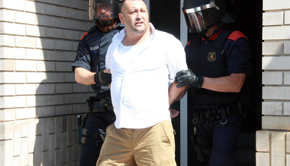 Un dels detinguts escortats per dos Mossos d'Esquadra a la sortida d'un dels domicilis registrats del barri del Temple de Tortosa.