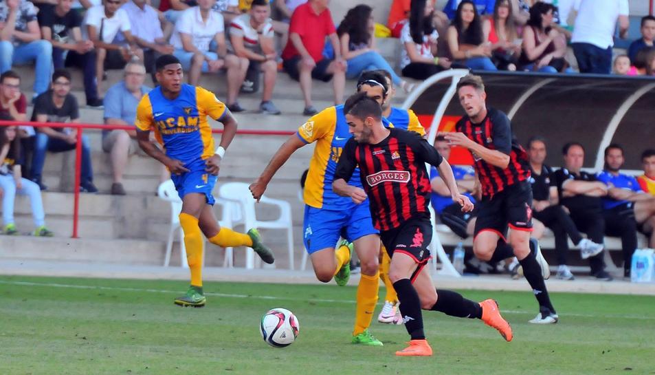 Fran Carbia  avança amb la pilota sota la mirada d'Edgar Hernández.