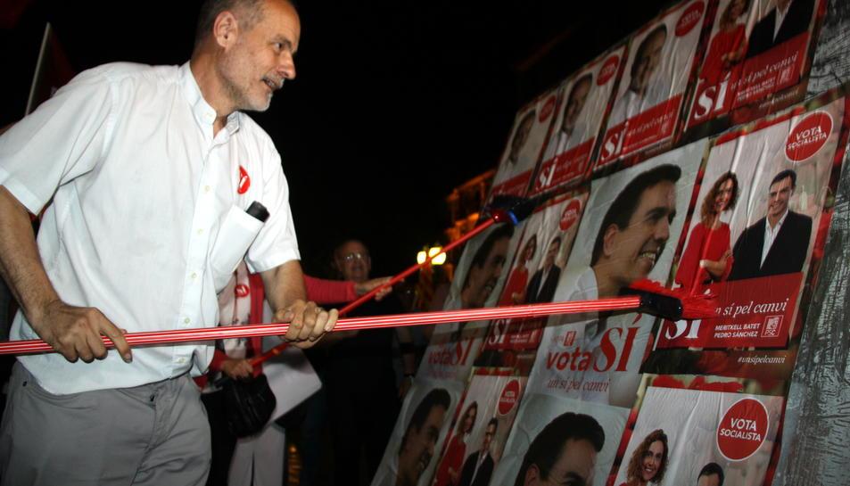 El cap de llista del PSC per Tarragona, Joan Ruiz, enganxant un cartell amb una escombra a la Rambla Nova de Tarragona.