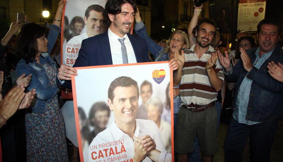 Pla obert del candidat de C's per Tarragona, Sergio del Campo, mostrant un cartell electoral amb el rostre d'Albert Rivera, envoltant de militants. Imatge del 10 de juny del 2016