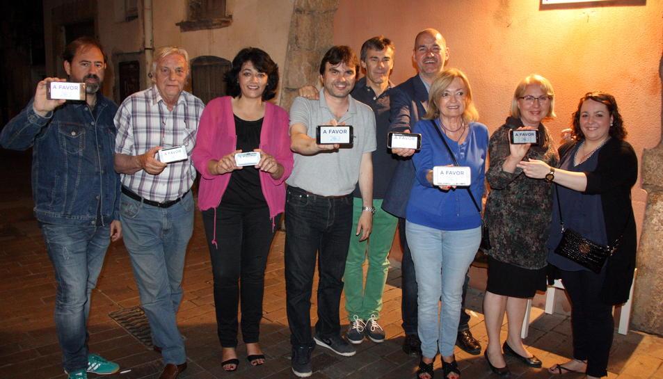 Pla general del cap de llista del PP, Jordi Roca, amb altres membres de la candidatura mostrant el lema de la seva campanya a les pantalles dels telèfons mòbils. Imatge del 10 de juny del 2016