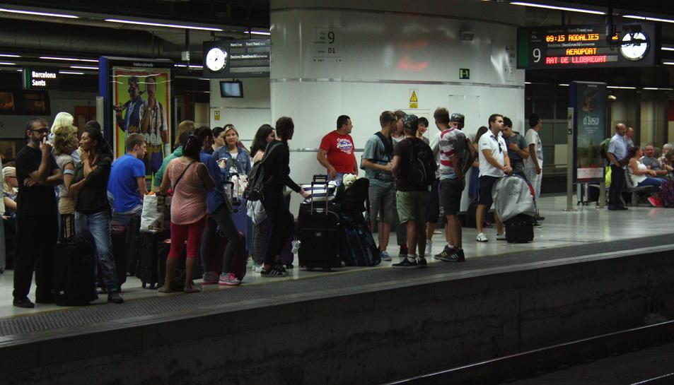Usuaris esperant el tren a l'andana de l'estació de Sants