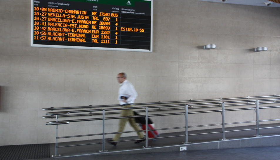 Un home amb una maleta passa per davant del panell que anuncia les sortides a l'estació de Tarragona el 10 de juny de 2016