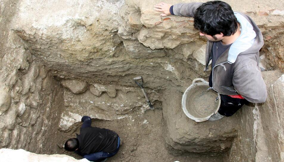 Un dels arqueòlegs treballant en l'excavació d'un sot al solar de la Catedral de Tortosa, amb l'ajuda d'un company des de la superfície.