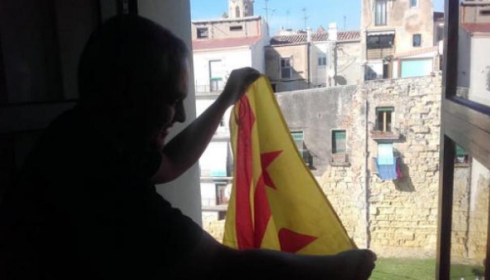El regidor de la CUP a l'Ajuntament de Tarragona, Jordi Martí, penjant una bandera estelada a la finestra del despatx.