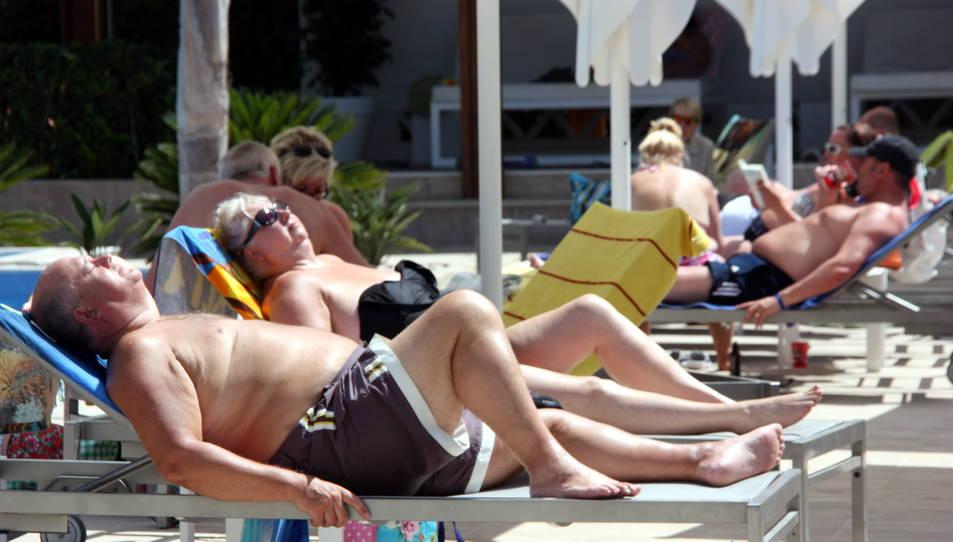 Una parella de turistes estrangers prenent el sol en unes gandules.