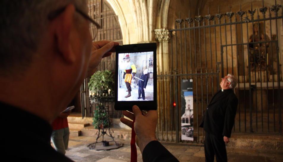 L'arquebisbe de Tarragona, Jaume Pujol, amb l'iPad a la mà, enfocant al degà-president del Capítol de la Catedral de Tarragona, Joaquim Fortuny, i al costat apareix, en realitat augmentada, un cavaller gegantí de l'època, Francisco Plaza