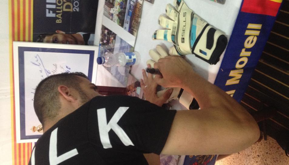 El futbolista, signant uns guants