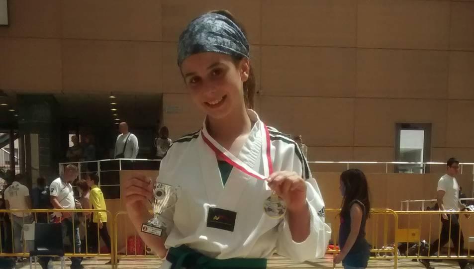 La jove, mostrant la medalla aconseguida.