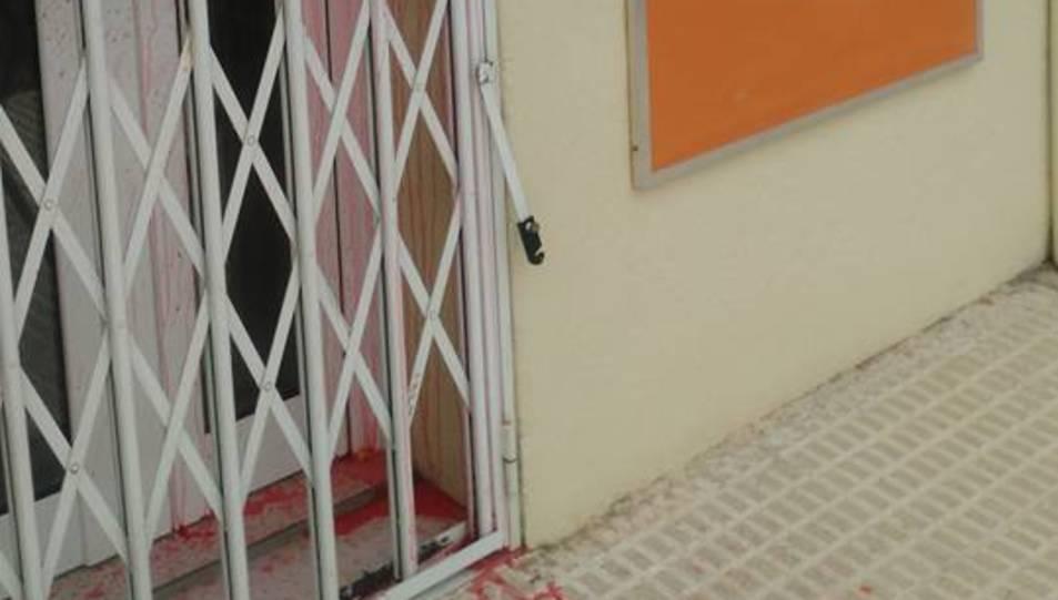 Imatge de la porta de la seu amb les marques de pintura