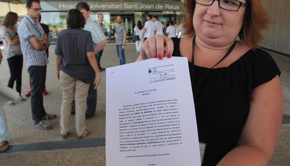 Una membre del comitè d'empresa de Ginsa, Noelia Macías, mostrant la demanda presentada al jutjat social de Reus, durant la protesta convocada davant l'hospital de Reus, el 5 de juliol de 2016