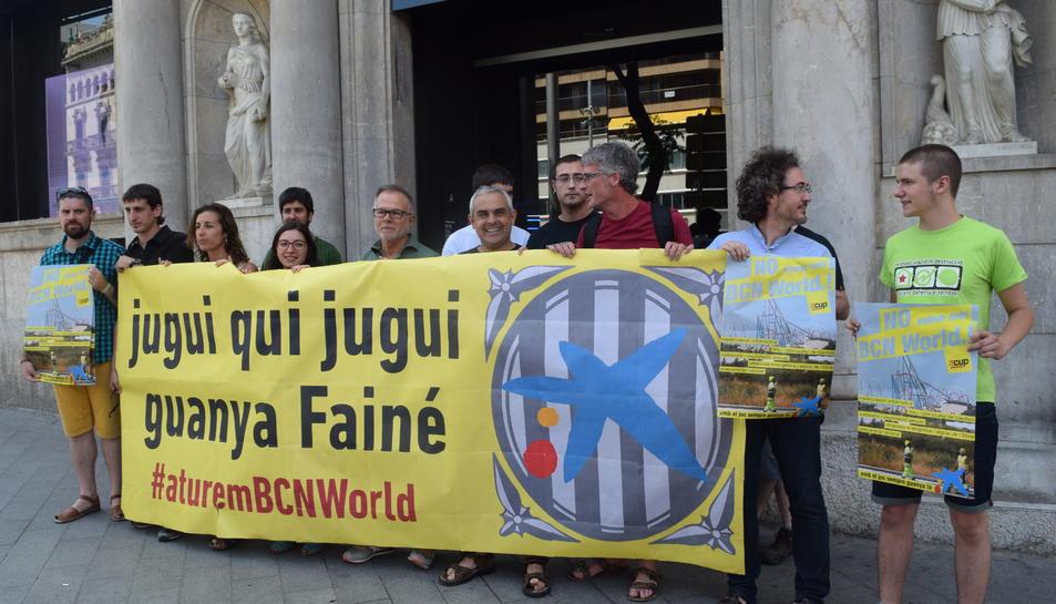 La formació anticapitalista va celebrar la roda de premsa davant d'una oficina de La Caixa.