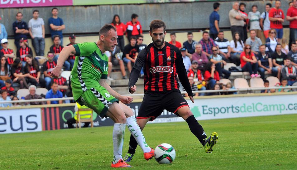 Migue, en un partit contra el Reus, lluitant per una pilota amb Alberto Benito