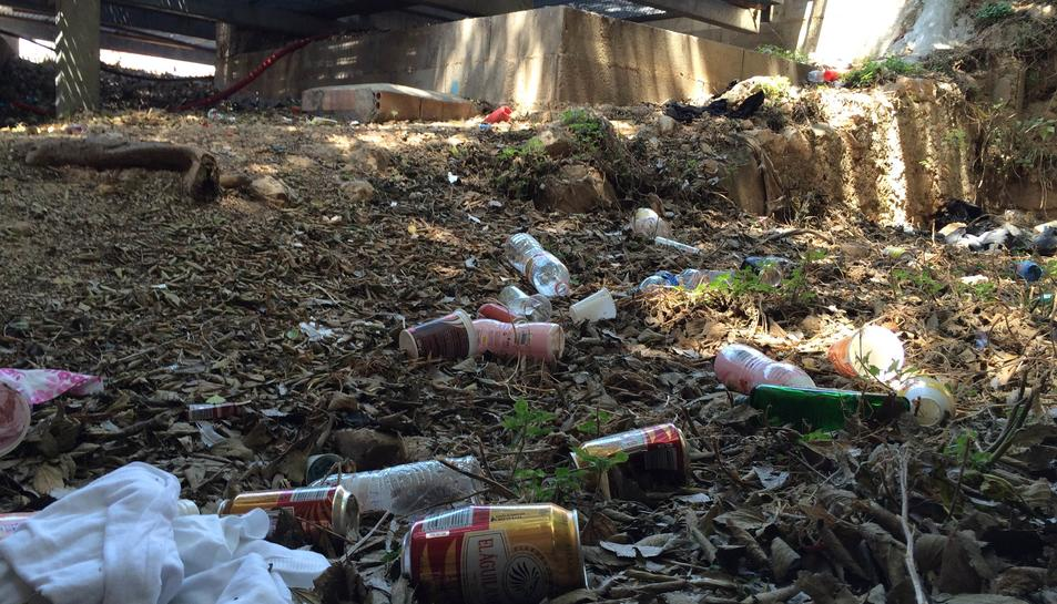 En un lateral de les escales s'acumulen peces de roba i desenes de llaunes i ampolles d'alcohol.