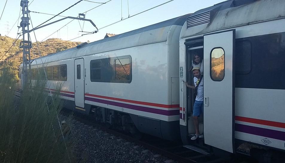 Usuaris d'un tren aturat entre Flix i Móra per una avaria d'electrificació a la línia esperen que els vinguin a rescatar per poder continuar el viatge el 18 de juliol del 2016. Pla general