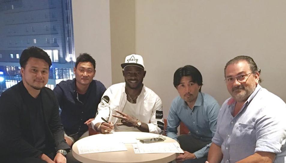 Imatge del jugador camerunès signant el contracte a Tokushima.