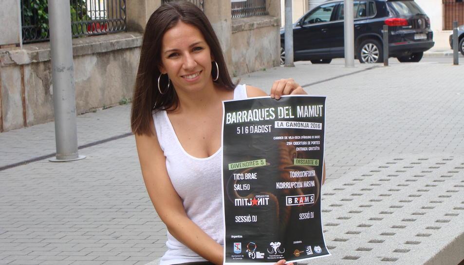 L'edil mostrant el cartell d'enguany del festival de música.