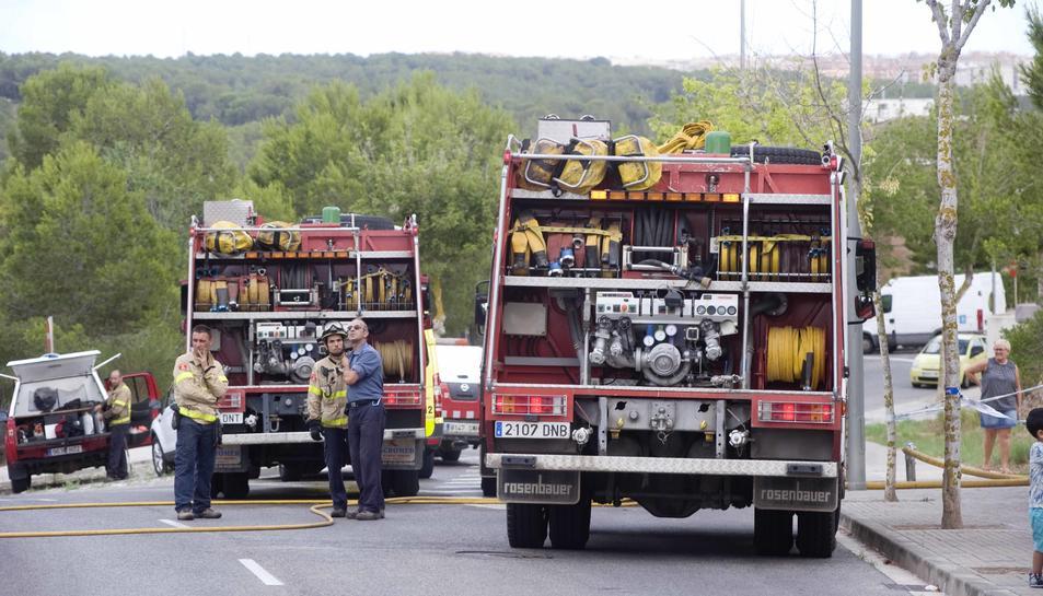 Membres del cos de bombers participant aquest dilluns en l'extinció d'un foc proper al barri.