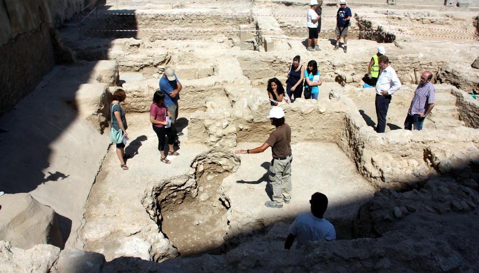 Zona on s'ha trobat una plaça del segle I mentre la visiten representants dels consistori, els directors de l'excavació i la premsa.