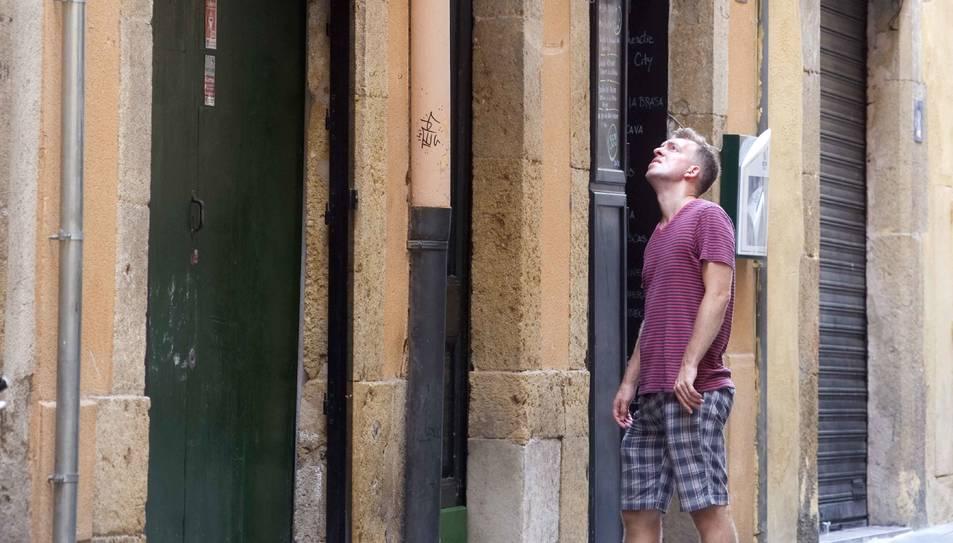 Un jove busca informació sobre pisos turístics al carrer la Nau.