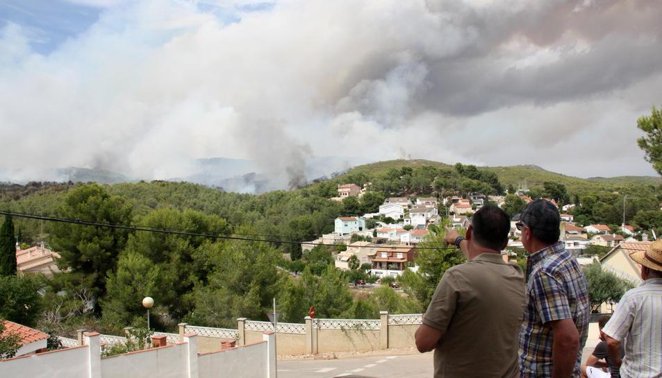 Dos veïns de La Pobla de Montornès observen i senyalen el fum i les flames de l'incendi que crema prop d'una urbanització del municipi. Imatge del 5 d'agost de 2016 (horitzontal)