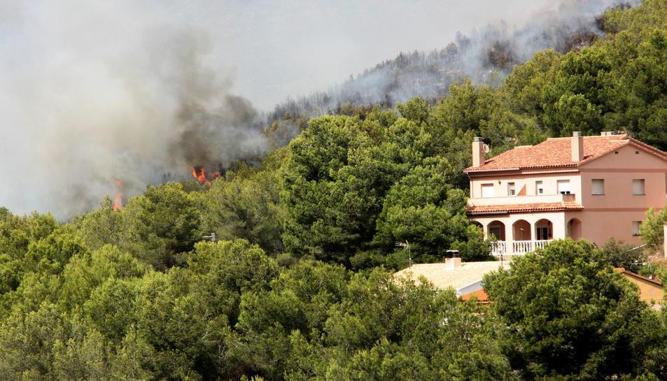 Pla general d'una casa enmig d'una zona boscosa de la Pobla de Montornès, on crema un incendi. Les flames apareixen darrere la finca. Imatge del 5 d'agost de 2016.
