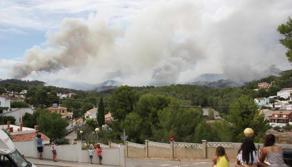Diversos veïns de la Pobla de Montornès contemplen la columna de fum de l'incendi. Imatge del 5 d'agost de 2016