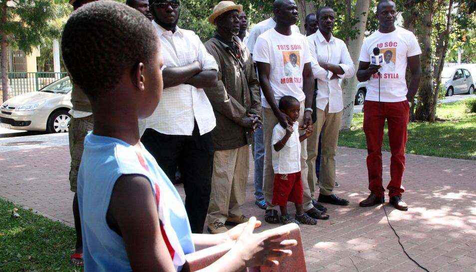 Pla general d'un grup de senegalesos i del germà de Mor Sylla sent entrevistat per una televisió senegalesa, amb un nen en primer terme, d'esquenes, l'11 d'agost a la plaça de la Pau de Salou