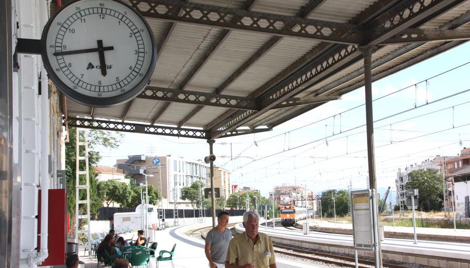 El rellotge de l'estació de Tortosa mentre arriba un dels trens des de Barcelona amb retard.